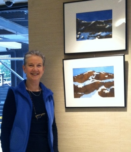 """Ruth Hurd standing next to two of her """"winter"""" paintings hanging in the lobby"""